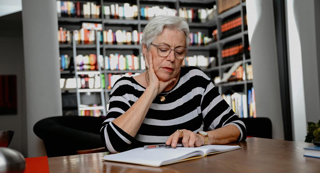 Ulrike Burkert liest vor ihrem Bücherregal